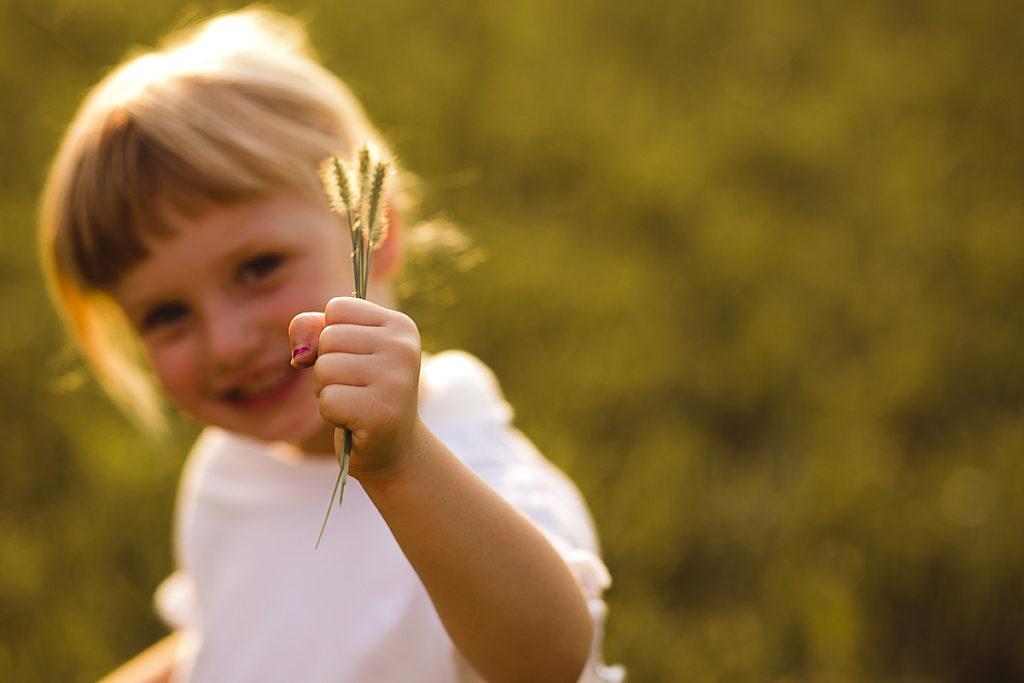 bimba sorridente con erba
